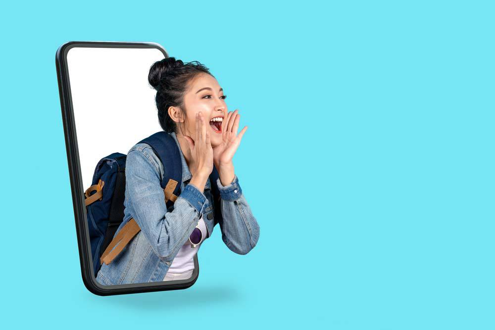Happy young girl coming out of mobile phone