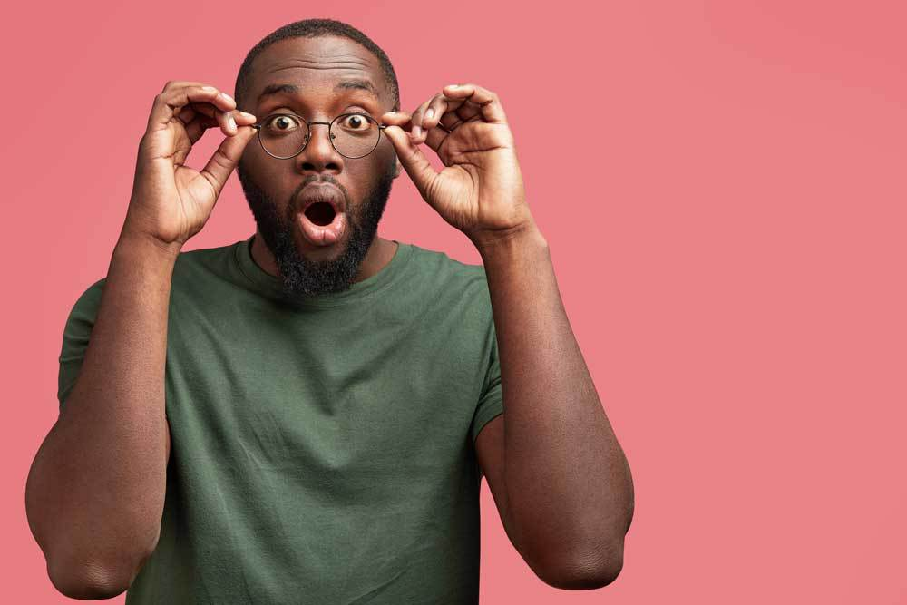 man taking off his glasses in surprise