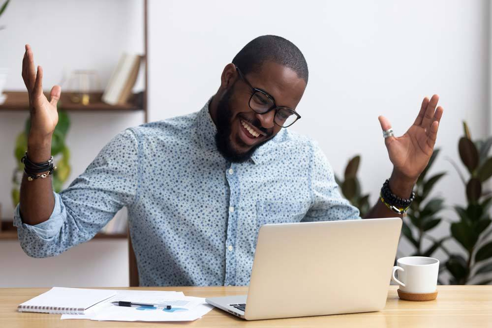 Man with raised hands is happy looking at the laptop